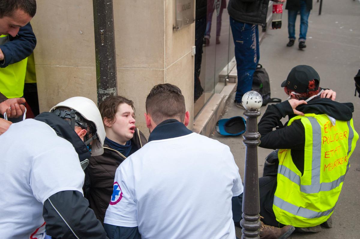 Une jeune fille incommodée par les gaz lacrymogènes cherche son souffle. - © Reflets