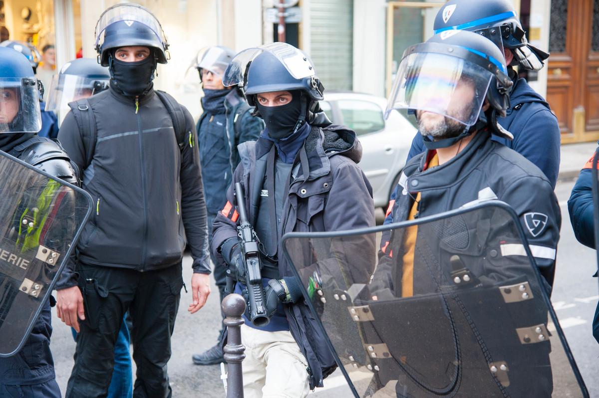 Comme les semaines précédentes, la présence de policiers en civil, non identifiés par un matricule est forte. Ils bloquent les rues qui permettraient d'approcher de la zone interdite. - © Reflets